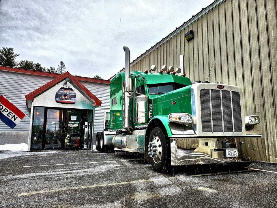 photo of green big rig truck cab in front of store front