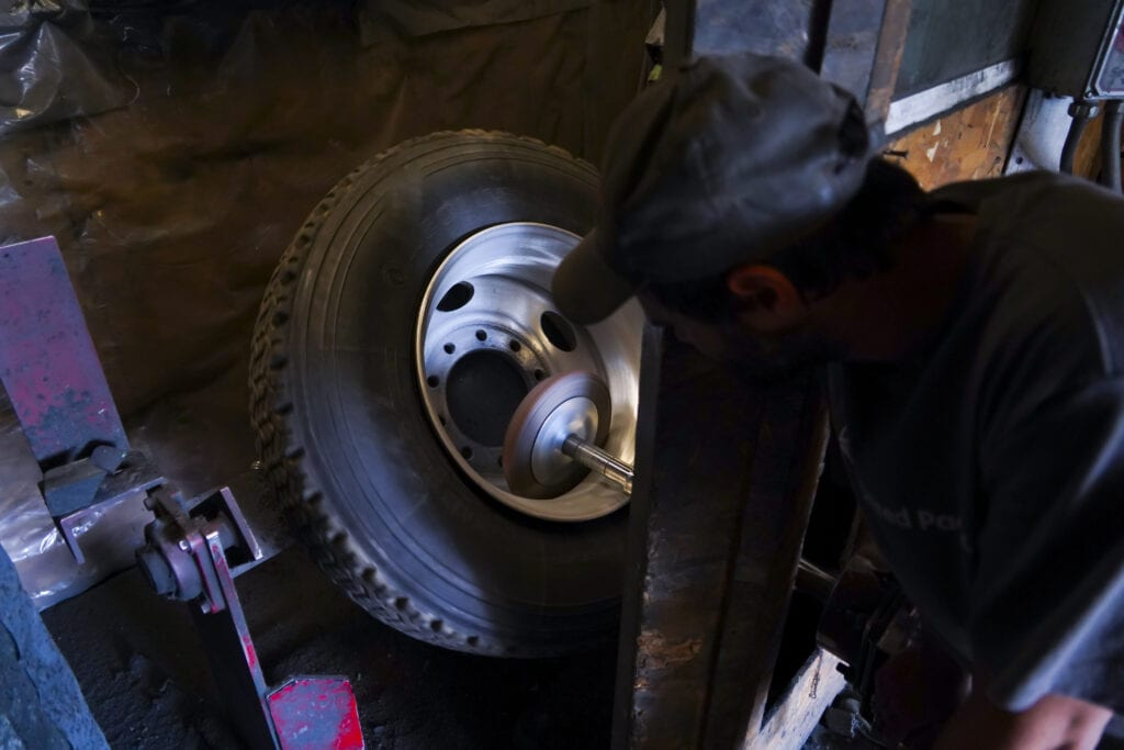 photo of man working in shop shining chrome wheel