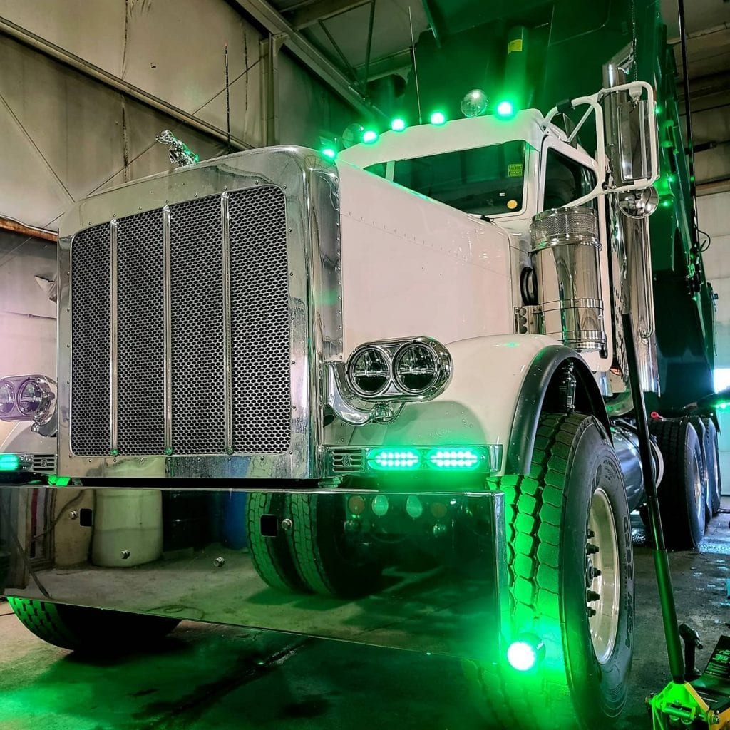 photo of big rig truck in garage with green lights