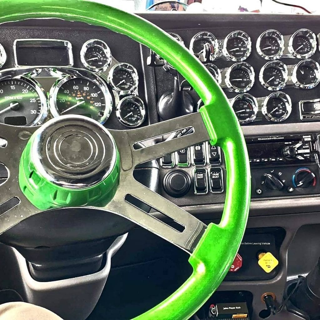 photo of big rig truck interior green steering wheel and dials