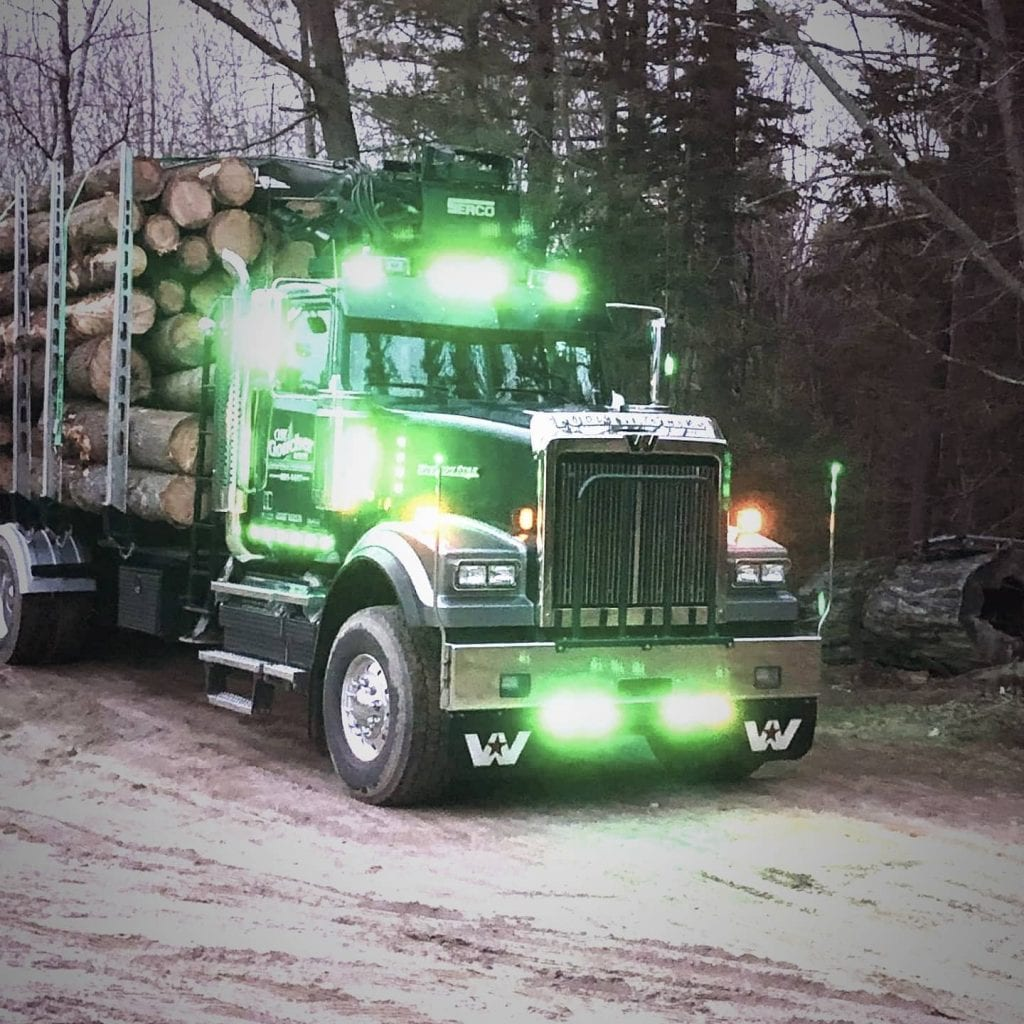 photo of big rig truck from the front with green logger lights